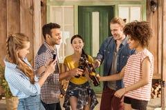 Groupe d'amis faisant tinter avec de la bière tandis que fille prenant la photo sur le smartphone Images stock