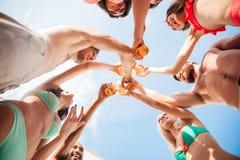 Groupe d'amis faisant tinter des bouteilles ensemble Photo libre de droits