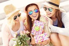 Groupe d'amis faisant un cadeau d'anniversaire de surprise Photo stock