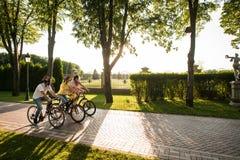 Groupe d'amis faisant un cycle sur la route en parc Image stock