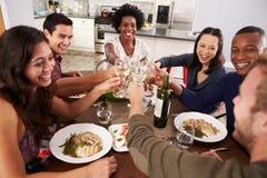 Groupe d'amis faisant un pain grillé au dîner Images libres de droits