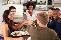 Groupe d'amis faisant un pain grillé au dîner Photos libres de droits