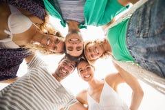 Groupe d'amis formant un petit groupe contre le ciel Photo stock
