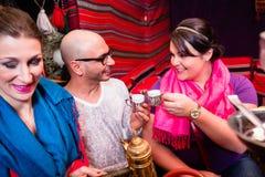 Groupe d'amis fumant le narguilé et buvant du café dans le salon de shisha Images libres de droits