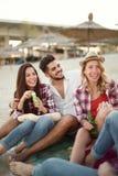 Groupe d'amis gais ayant le grand temps à la plage Photo stock