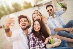 Groupe d'amis gais ayant le grand temps à la plage Photographie stock libre de droits