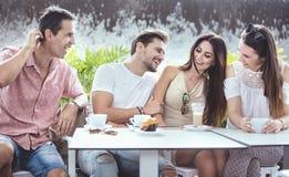 Groupe d'amis gais dans la maison de coffe Images stock
