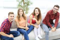 Groupe d'amis gais observant des vidéos, s'asseyant sur le divan Images stock