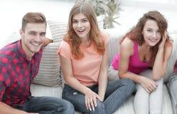 Groupe d'amis gais observant des vidéos, s'asseyant sur le divan Photographie stock