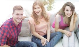 Groupe d'amis gais observant des vidéos, s'asseyant sur le divan Photographie stock libre de droits