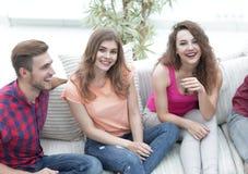 Groupe d'amis gais observant des vidéos, s'asseyant sur le divan Images libres de droits