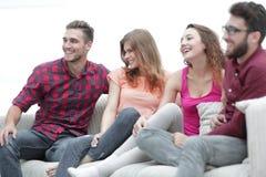 Groupe d'amis gais s'asseyant sur le divan Image stock