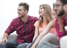 Groupe d'amis gais s'asseyant sur le divan Photographie stock