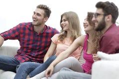 Groupe d'amis gais s'asseyant sur le divan Images stock