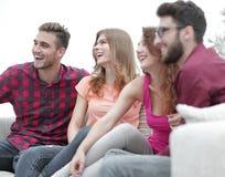 Groupe d'amis gais s'asseyant sur le divan Photo stock