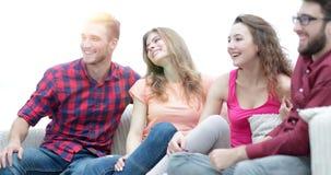 Groupe d'amis gais s'asseyant sur le divan Images libres de droits