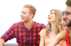 Groupe d'amis gais s'asseyant sur le divan Photos libres de droits