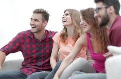 Groupe d'amis gais s'asseyant sur le divan Photographie stock libre de droits