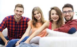 Groupe d'amis gais s'asseyant sur le sofa Images libres de droits