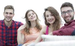 Groupe d'amis gais s'asseyant sur le sofa Photographie stock