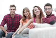 Groupe d'amis gais s'asseyant sur le sofa Photo stock