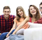 Groupe d'amis gais s'asseyant sur le sofa Photos stock