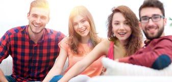 Groupe d'amis gais s'asseyant sur le sofa Photo libre de droits