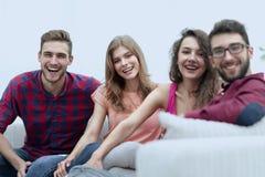Groupe d'amis gais s'asseyant sur le sofa Image stock