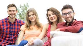 Groupe d'amis gais s'asseyant sur le sofa Image libre de droits