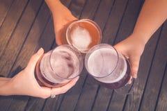 Groupe d'amis grillant avec de la bière à la table Photo stock