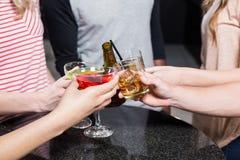 Groupe d'amis grillant avec de la bière et des cocktails Image libre de droits