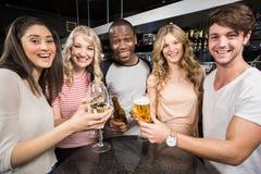 Groupe d'amis grillant avec de la bière et le vin Image stock