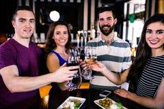 Groupe d'amis grillant avec un verre de vin Photos stock
