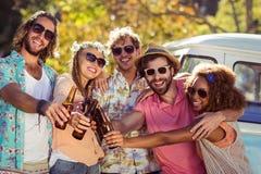 Groupe d'amis grillant des bouteilles à bière Photos libres de droits