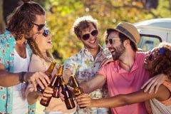 Groupe d'amis grillant des bouteilles à bière Photographie stock