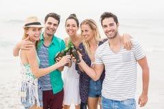 Groupe d'amis grillant des bouteilles à bière sur la plage Photos libres de droits