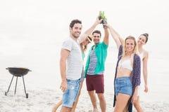 Groupe d'amis grillant des bouteilles à bière sur la plage Images libres de droits