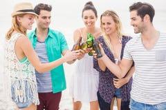 Groupe d'amis grillant des bouteilles à bière sur la plage Photographie stock
