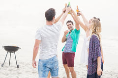 Groupe d'amis grillant des bouteilles à bière sur la plage Photo stock