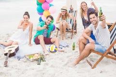 Groupe d'amis grillant des bouteilles à bière sur la plage Image stock