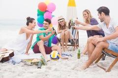 Groupe d'amis grillant des bouteilles à bière sur la plage Photographie stock libre de droits