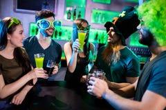 Groupe d'amis grillant des tasses de bière et des verres de boissons Photographie stock libre de droits