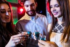 Groupe d'amis grillant des verres à liqueur de tequila Photographie stock libre de droits
