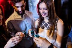 Groupe d'amis grillant des verres à liqueur de tequila Photographie stock