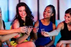 Groupe d'amis grillant des verres à liqueur de tequila Image libre de droits