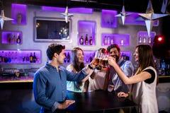 Groupe d'amis grillant des verres de bière au compteur de barre Image libre de droits