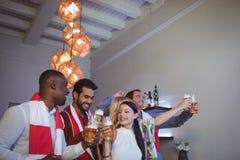 Groupe d'amis grillant des verres de bière tout en regardant la rencontre Image stock