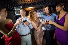 Groupe d'amis grillant des verres de champagne et de vin Photos libres de droits