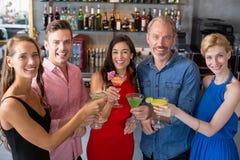 Groupe d'amis grillant des verres de cocktail Photographie stock