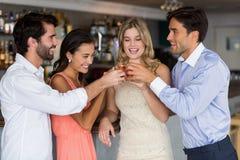 Groupe d'amis grillant des verres de tir de tequila Photos stock